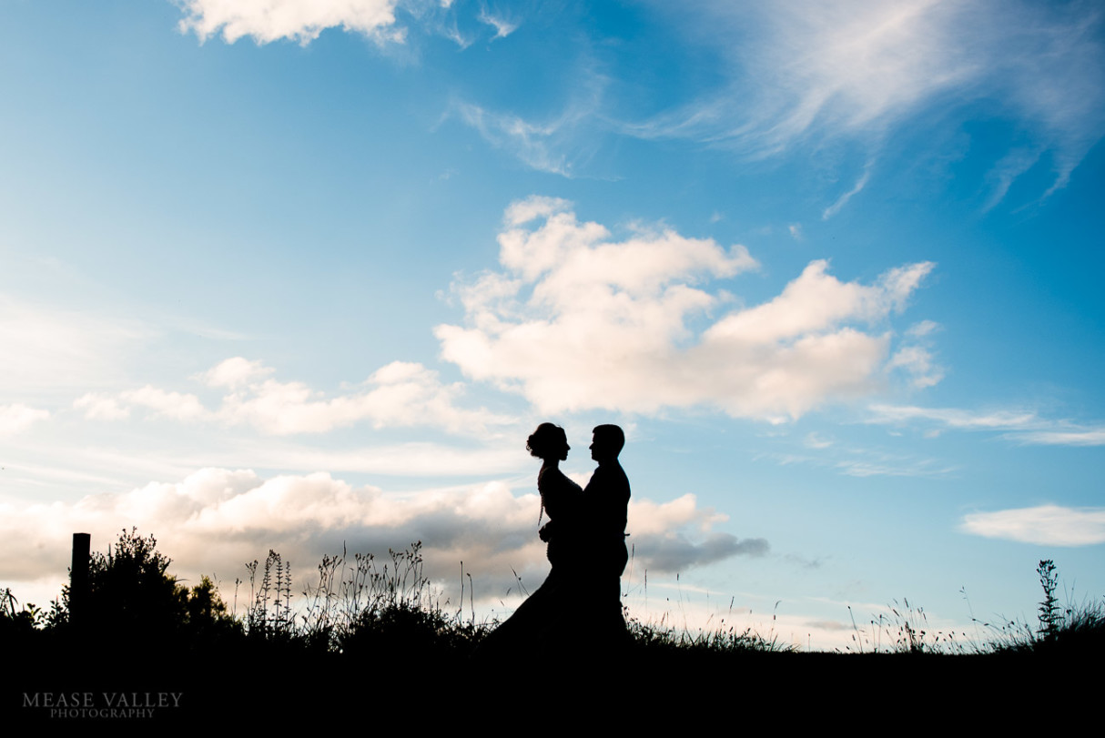 Photograph of bride and groom silhouetted against the sky on their wedding day.