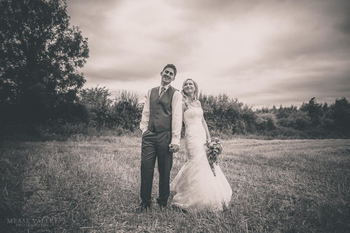 Black and white picture of bride and groom in field